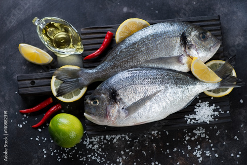 Fotografie, Obraz  Couple of fresh uncooked sea breams with seasonings on a black wooden cutting bo