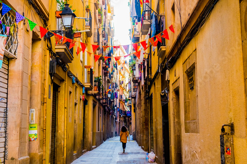 fototapeta na drzwi i meble woman walks in old street in old center of barcelona in spring day
