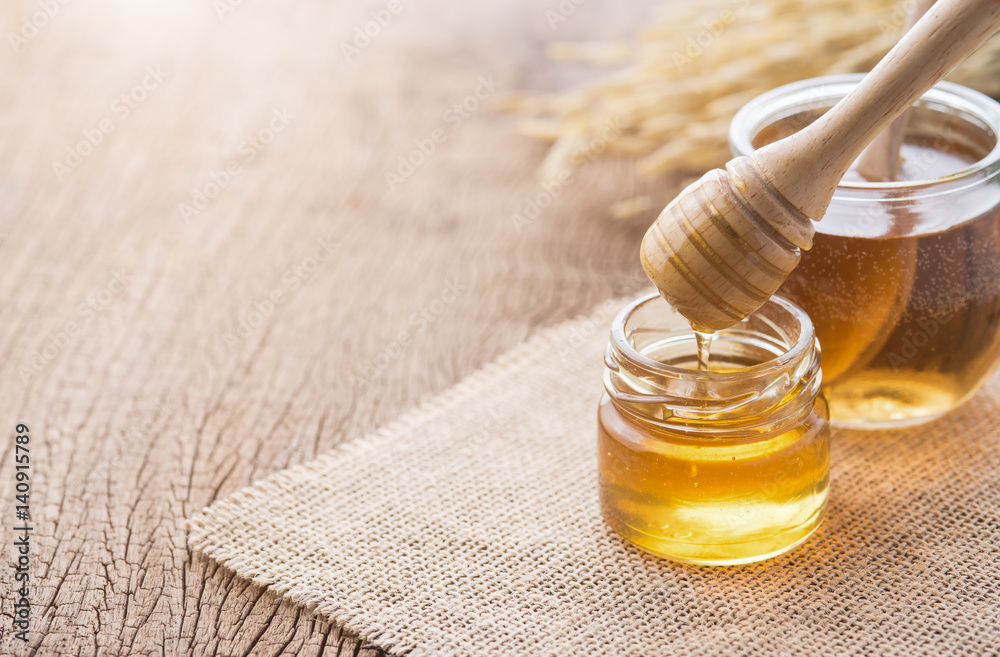 Fototapety, obrazy: Honey with wooden honey dipper on wooden table