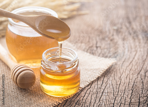 Fotografija Honey with wooden honey dipper on wooden table