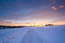 Sunset Over A Snow Covered Road  In A Rural Area Of York County, Pennsylvania.