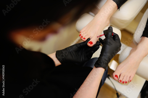 The nail wizard makes a pedicure to a girl. To paint nails in red color