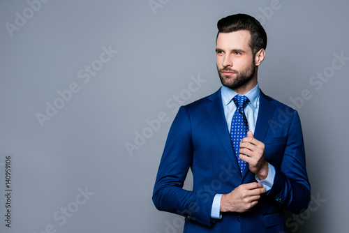 Fotomural Portrait of serious fashionable handsome man in blue suit and tie  buttoning cuf