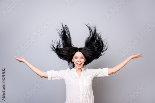 Portrait of charming smiling lady in white shirt with flying hair