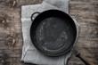 Empty black cast-iron frying pan on a textile napkin