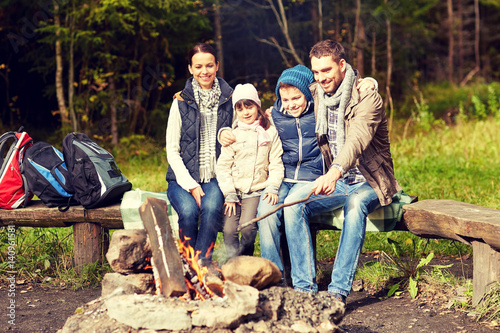 Foto auf AluDibond Camping happy family sitting on bench at camp fire