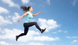 happy sporty young woman jumping in blue sky