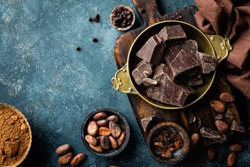 Komadići tamne čokolade zdrobljeni i zrna kakaa, kulinarska podloga, pogled odozgo