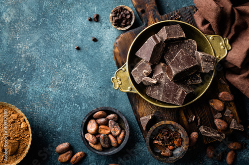 Fotografija Dark chocolate pieces crushed and cocoa beans, culinary background, top view