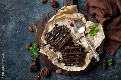 Spoed Foto op Canvas Dessert Chocolate brownie cake, dessert with nuts on dark background, directly above, flat lay