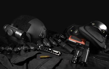 Black military ammunition tactical gun, helmet, gloves, cartridge belt, bandolier, gun shell, knife, binocular and knee protection laying on a black table.
