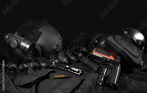 Fotografía  Black military ammunition tactical gun, helmet, gloves, cartridge belt, bandolier, gun shell, knife, binocular and knee protection laying on a black table