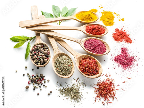 Fotografía  Assortment of colorful spices in the wooden spoons on the white background