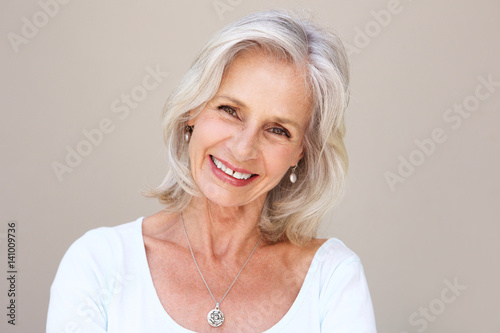 Photo  beautiful older woman smiling and standing by wall