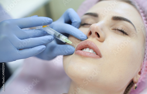 Woman gets injection in her face  Beauty woman giving