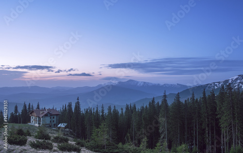 Spoed Fotobehang Zalm House at a mountain hill at sunrise. Hut in a forest with view at a mountain range at sunrise
