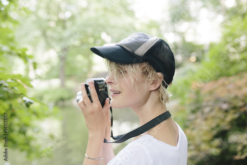 Tuinposter Retro Young Female Student Taking Pictures with a Vintage Camera in Central Park, Manhattan, New York City US