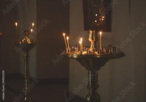 Foto op Plexiglas Wand lighting candles in a church