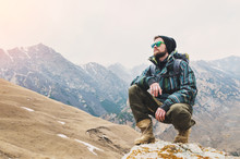 Tired Bearded Hipster With Binoculars In His Hands Sits On A Stone Among The Mountains And Looks Out Into The Distance