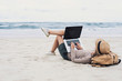 canvas print picture - Young woman using laptop computer on a beach. Freelance work concept