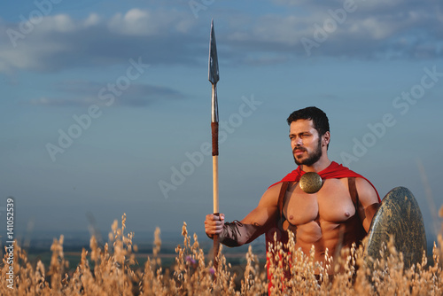 Photo  Handsome warrior going in attack with rounded shield.