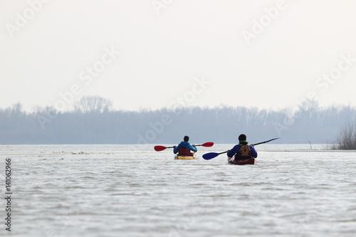 Valokuva  Two guys in kayaks in winter Danube river. Winter kayaking