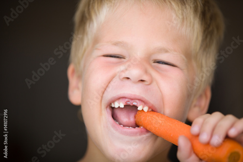 Portrait of cute toothless kid boy eating carrot Canvas Print