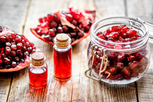 Sliced Pomegranate And Extract In Glass On Wooden Background