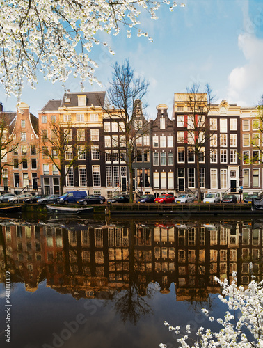 Photo  Facades of dutch houses over canal with mirror reflections at blooming, Amsterda