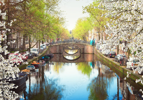 Photo  row of bridges over canal with mirror reflections in water, Amsterdam in bloomin