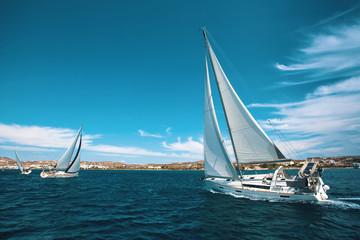 Luxury yachts at regatta. Sailing through the waves at the Aegean Sea.