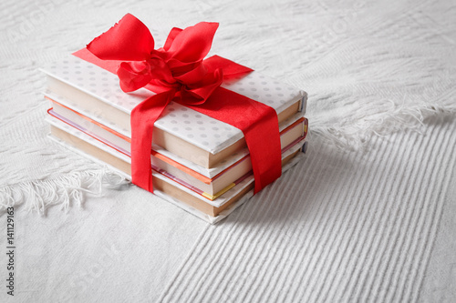 Fotografía  Gift books beautifully wrapped and bandaged with a red ribbon bow on a white cov