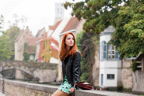 Wall Murals Bridges beautiful young woman sitting on the stone fence and exploring the town