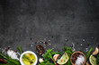 Leinwandbild Motiv Selection of spices herbs and greens. Rosemary basil lemon olive oil pepper top view black background.