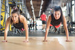 Two sporty girls doing push ups while their legs are on suspension strap at gym.