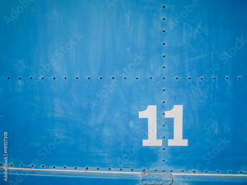 Fotografia  Number eleven in white with blue background and rivets, beautiful background wit