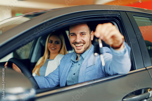 Young couple holding the keys of a new car