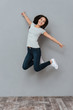 Vertical image of smiling woman jumping in studio