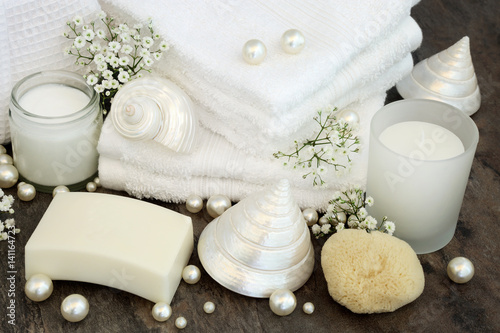 Poster Spa Body Care Cleansing Products. With white bathroom accessories, moisturising cream, soap, white flannels, natural sponge, candle, mother of pearl shells and pearls.