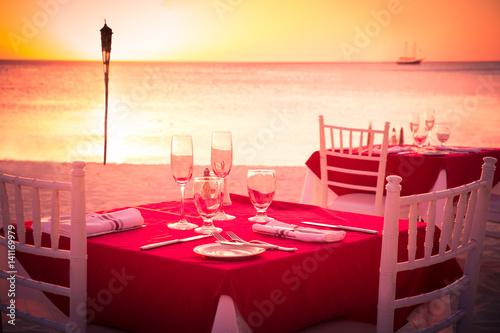 Table on beach set for romantic sunset dinner
