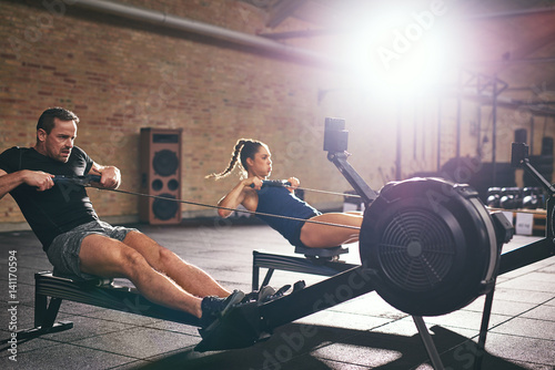 Two people training on rowing machines together Canvas