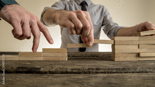 Obraz Businessman building staircase with wooden blocks to span a gap for partner - fototapety do salonu