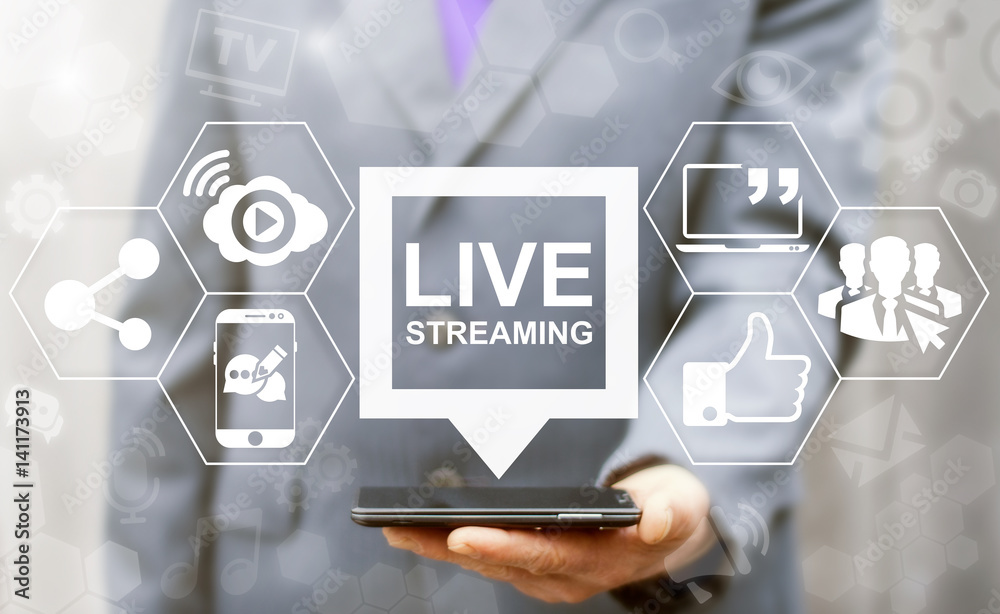 Fototapeta Live streaming social media web network concept. Man offers smart phone with bubble live streaming icon on virtual screen. Broadcast online technology stream video and music. Internet marketing.