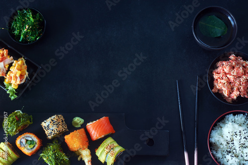 Fotomural  Top view of  assorted sushi rolls with salmon, avocado and wakame, crab meat, wakame salad, bowl of rice, green tea and chopsticks over black background