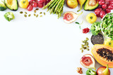 Fototapeta Fototapety do kuchni - Clean-eating food frame with copy space. Top view of papaya, avocado, tomato, grape, asparagus, figs, broccoli, goji, chia, pumpkin seeds on white background.
