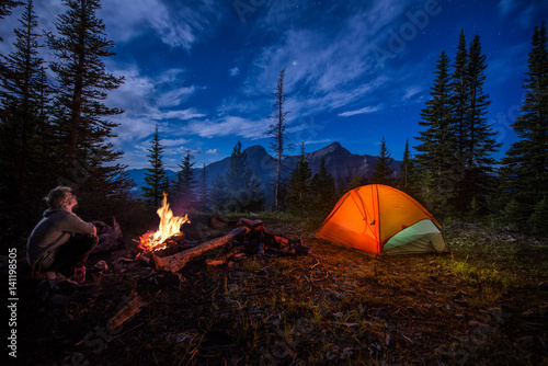 Man looking up at the stars next to campfire and tent at night Fotobehang