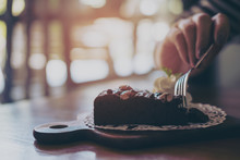 A Woman's Hand Cutting Brownie Cake With Fork In Vintage Wooden Cafe