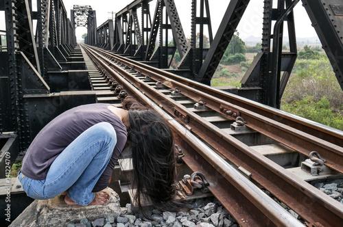 Desperate woman alone beside railway in foetal position, depression, sadness, su Fototapeta