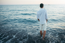 Horizontal Back View Of Man Wearing White Shirt And Pants On The Beach And Sea Background. Travel Vacation Holiday. Man Walking Barefoot At The Sea. Relax Caucasian Man Model Looking Away, Freedom.