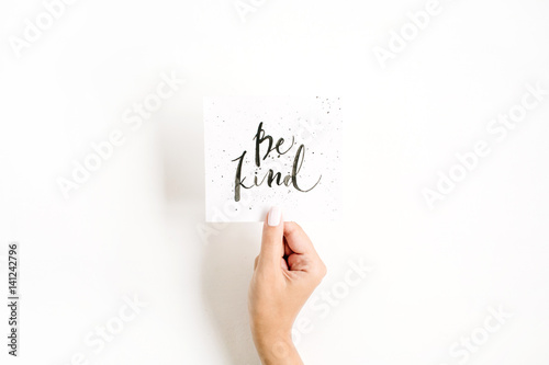 Fotografia Minimal pale composition with girl's hand holding card with quote Be Kind written in calligraphic style on paper on white background